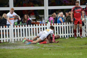 Cpl Alex Swann scoring a try in goal carrying an opposition player in the process