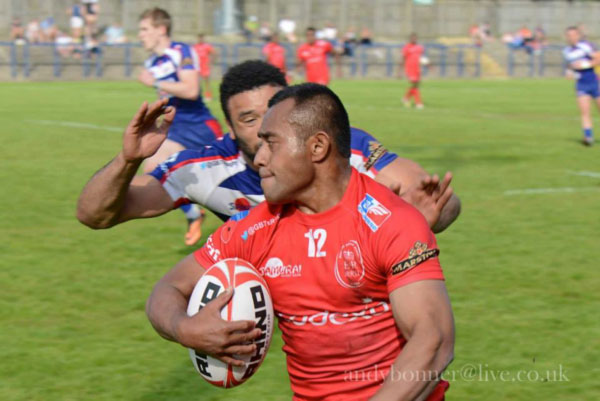 Cpl Zack Vakasawaqa showing a shoulder to protect the ball for his scoring run under the posts